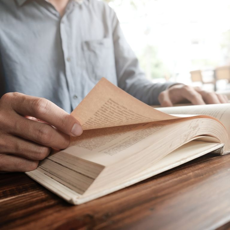 midsection-of-man-reading-book-on-table-royalty-free-image-948805758-1551877166